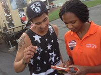 Outreach worker Emanuela Cebert (right) talks to Papilon Ferreiras about health insurance outside a rap concert.