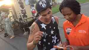 Outreach worker Emanuela Cebert (right) talks to Papilon Ferreiras about health insurance outside a rap concert.