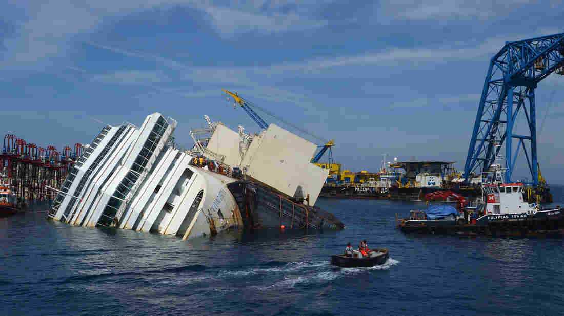 Salvage workers prepare the Costa Concordia cruise ship on Aug. 23 in the waters of the Tuscan island of Giglio. The massive cruise ship has lain partially submerged after a disaster on Jan. 13, 2012, that killed 32 people.