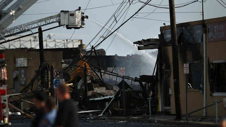 A firefighter on Friday sprays water on a hot spot at the scene of a massive fire that destroyed dozens of businesses along the Jersey Shore boardwalk.