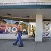 A man walks past a Democratic campaign office (left) and a pro-gun-group's office, which display signs against, and in favor of, recalling Democratic state Sen. Angela Giron, on the day of the Sept. 10 recall vote in Pueblo, Colo.