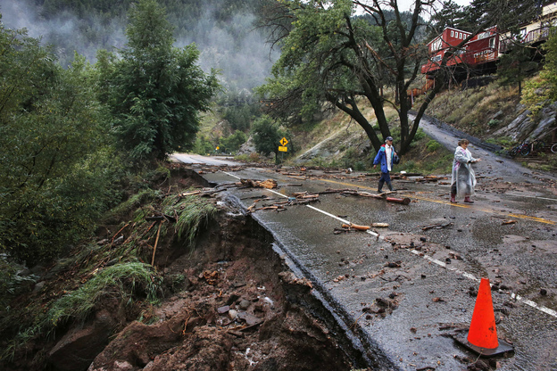 Patrick Tinsley and Mary Kerns walk from their mountain community, Magnolia, where road access is shut off by debris. Flash flooding in Colorado has left at least three people reportedly dead and the widespread high waters have hampered emergency workers' access to affected communities as heavy rains hammered northern Colorado. (AP)