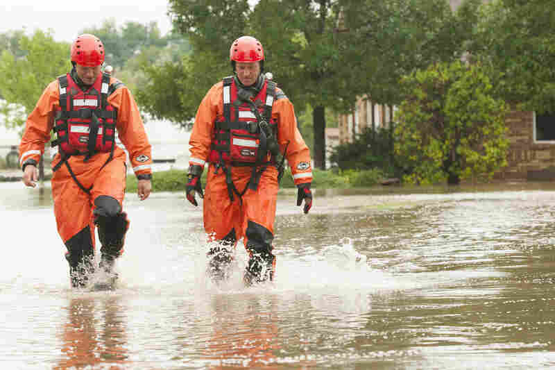 Mountain View Fire Rescue firefighters Jamie Wood and Steve Knoll walk through a flooded street after doing a welfare check of a flooded property in Erie, Colo.