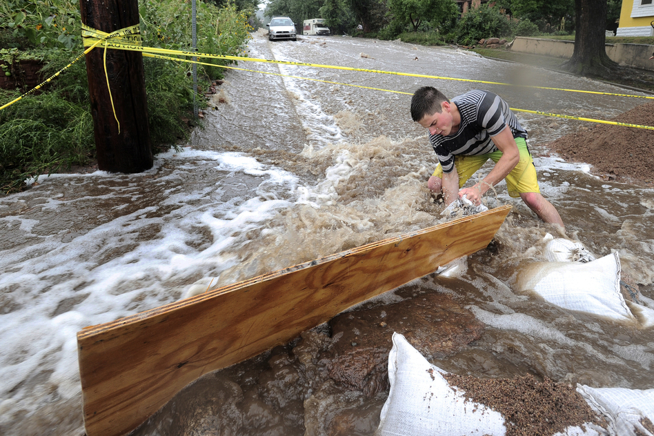 Jake Bennett uses sandbags and plywood to help funnel water down a street in Boulder. (Reuters/Landov)