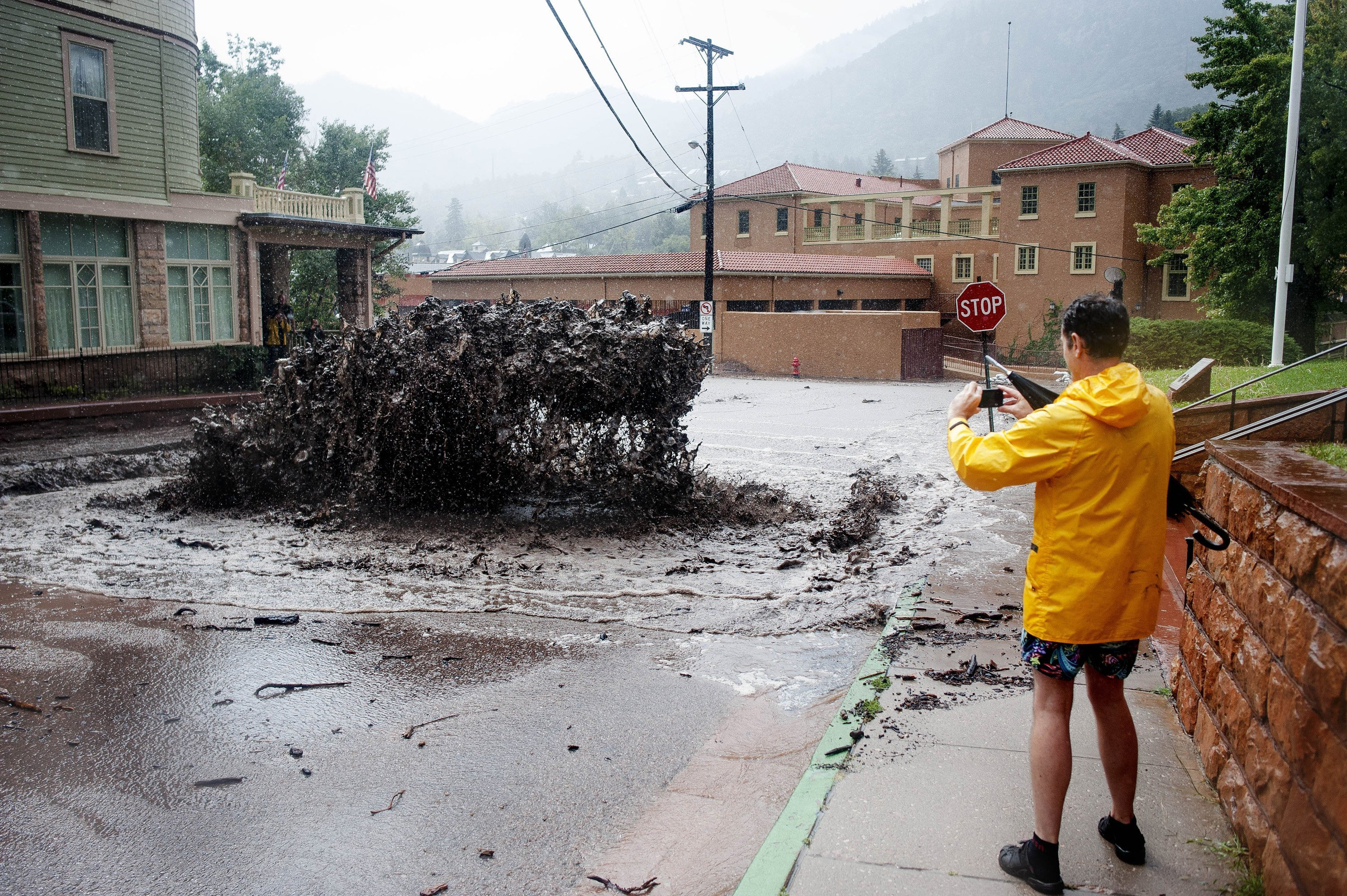 John Shada takes a photo as a geyser of floodwater shoots out of a sewer in Manitou Springs.
