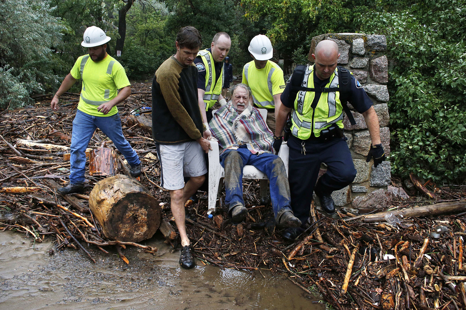 Will Pitner is rescued by emergency workers and neighbor Jeff Writer on Friday, after a night sheltering on high ground above his home as it filled with water from a surge at the base of Boulder Canyon, Colo. (AP)