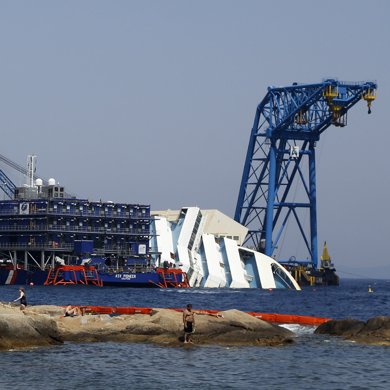 People sunbathe in front of the capsized Costa Concordia outside Giglio harbor, on Aug. 8. The cost of the salvage operation -- one of the biggest in history -- could exceed $1 billion.