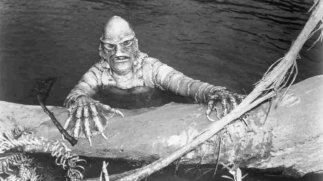 "A scene from the film Creature From the Black Lagoon, with the monster ""The Gill Man"" (played by Ben Chapman) emerging from the murky waters onto a log."