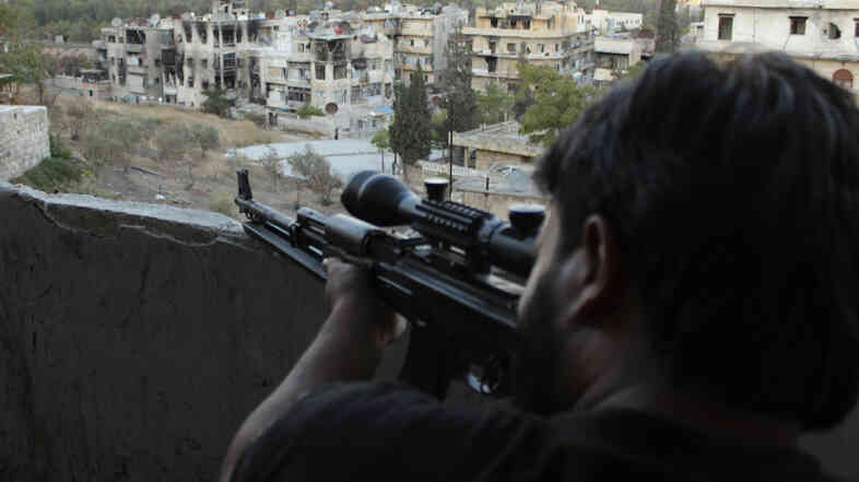 A Free Syrian Army fighter looks through the scope of his sniper rifle at an area controlled by forces loyal to President Bashar Assad in Aleppo.