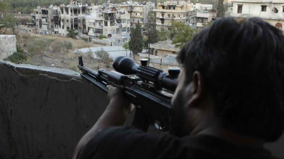 A Free Syrian Army fighter looks through the scope of his sniper rifle at an area controlled by forces loyal to President Bashar Assad in Aleppo. (Reuters/Landov)