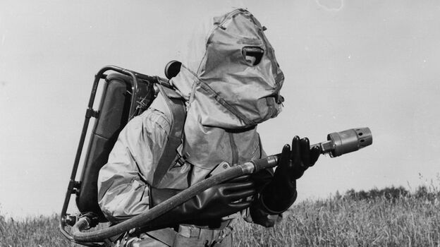 A U.S. Marine carries a light flame-thrower while wearing experimental clothing designed to protect against atomic, biological and chemical warfare in 1960. (Getty Images)