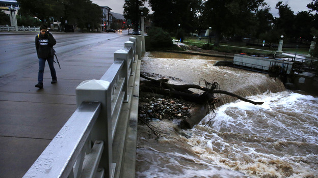 A woman walks past Boulder Creek, whose swollen waters have receded a bit after intense rain that fell for days has abated, in Boulder, Colo., Sunday. (AP)