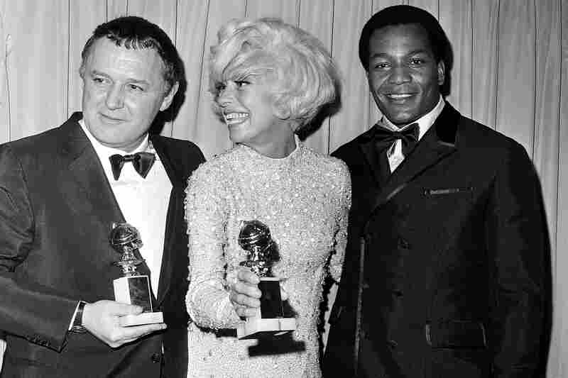 Rod Steiger (left) and Channing are presented with Golden Globes in 1968 by former football star Jim Brown. They won for best actor in a motion picture drama and best supporting actress.
