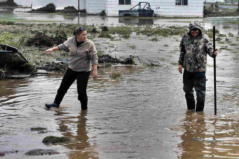 Miranda Woodard and Joey Schendel salvage and clean property after days of flooding in Hygiene, Colo. Mountain towns that had been cut off for days by massive flooding slowly reopened Monday, to reveal cabins toppled, homes ripped from their foundations and everything covered in a thick layer of muck.