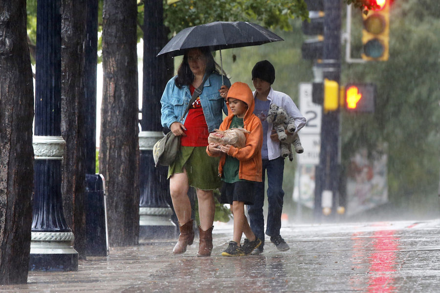 A woman walks with her two boys in Longmont on Sunday. Forecasters said more rain was expected Monday across Colorado's Front Range and the weather likely wouldn't clear up until Wednesday or Thursday.