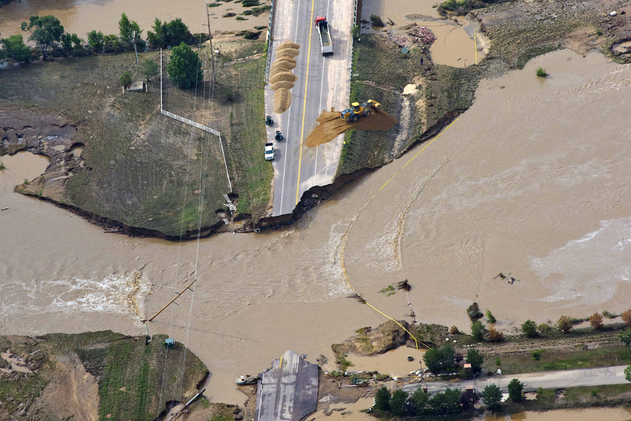 A road crew works on a stretch of highway washed out by flooding along the South Platte River in Weld County on Saturday. Hundreds of roads in the area have been damaged or destroyed by the floodwaters, which affected parts of a 4,500-square-mile area.