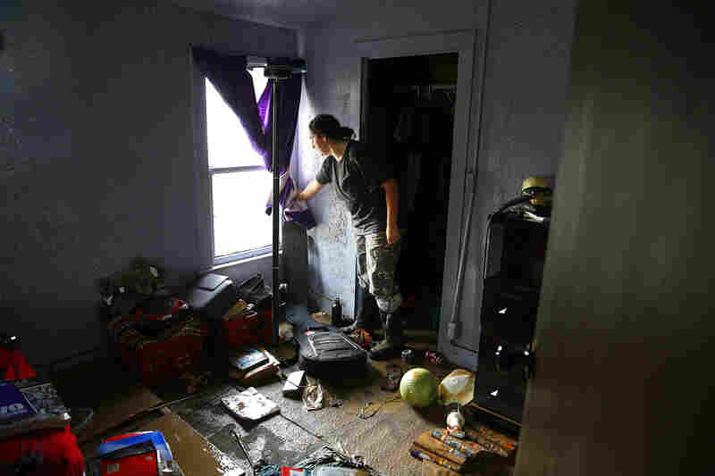 Julie DeGraff pulls back a curtain to reveal the damage inside her home in La Salle, which had more than a foot of standing water inside. The historic flooding forced thousands to evacuate the area.