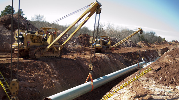 A 60-foot section of pipe is lowered into a trench during construction of the Gulf Coast Pipeline in Prague, Okla., in March. The Gulf Coast Pipeline, a 485-mile crude oil line, is part of the Keystone XL project and will run from Cushing, Okla. to Nederland, Texas. Although this southern stretch of the pipeline is nearly finished, the northern stretch is still under study. (Bloomberg via Getty Images)