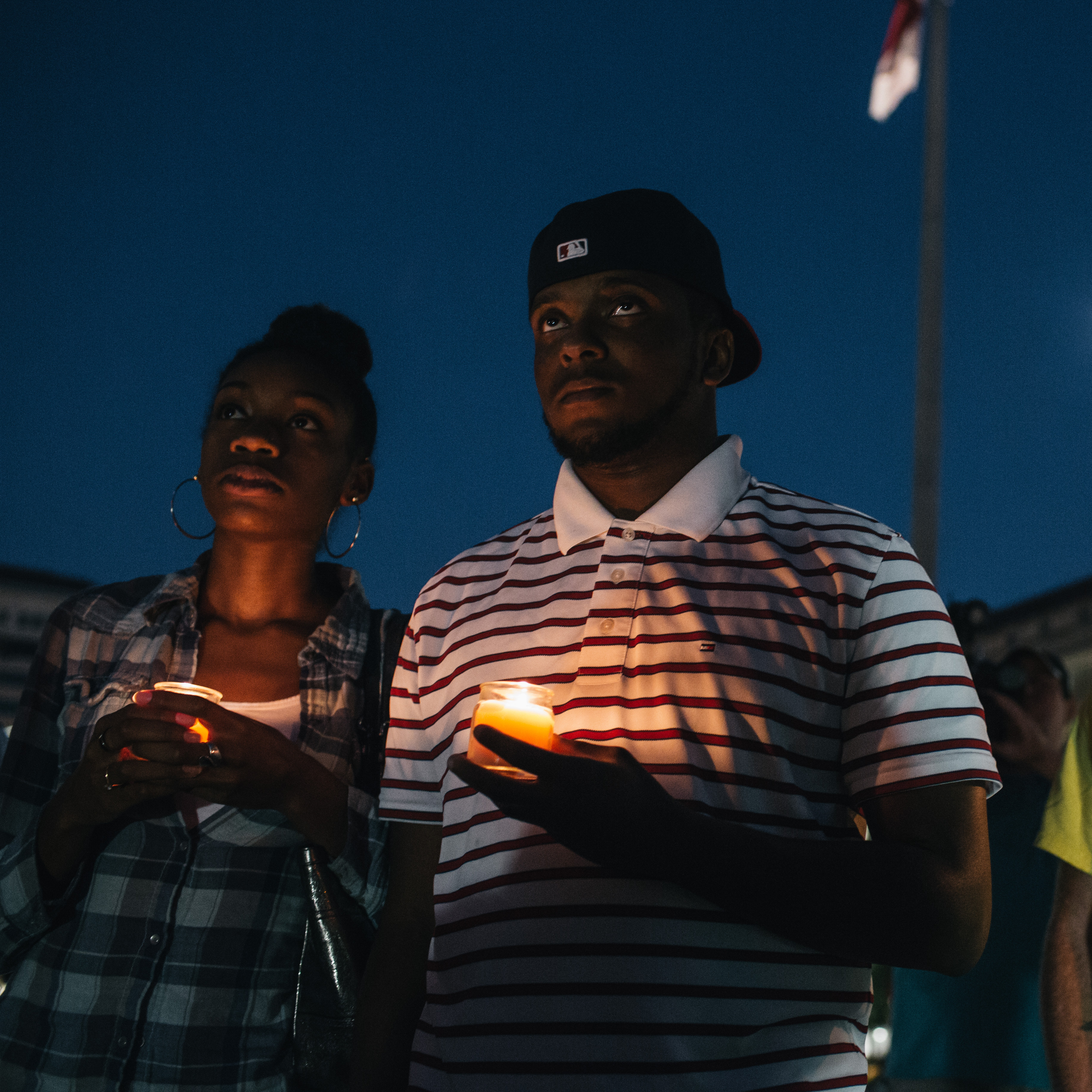 Brittany Carter, of Bowie, MD., (left) Jibri Johnson, of Landon, MD., (center) and Bryan Beard of Washington D.C. hold candles in remembrance of the 12 victims killed in a shooting at the Washington Navy Yard earlier in the day.
