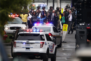 Workers emerge from a building after a deadly shooting at the Navy Yard. Alexis's motive is still uncertain but, D.C. Mayor Vincent Gray said in a press conference that there is