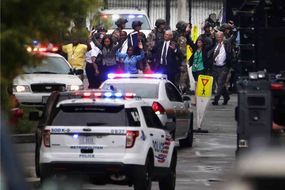 "Workers emerge from a building after a deadly shooting at the Navy Yard. Alexis's motive is still uncertain but, D.C. Mayor Vincent Gray said in a press conference that there is ""no reason to suspect terrorism."""
