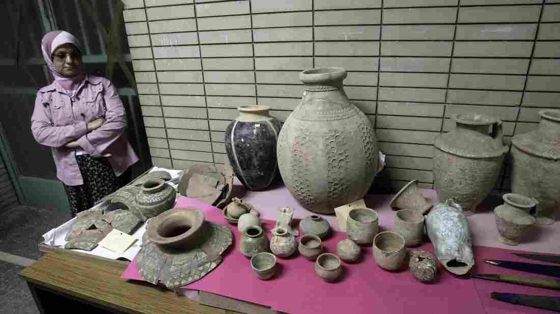 A woman stands next to a display of recovered antiquities at the Iraqi National Museum in Baghdad, Iraq on April 27, 2008. The Iraqi National Museum has welcomed home 701 artifacts that were stolen during looting after Saddam Hussein's ouster in 2003.