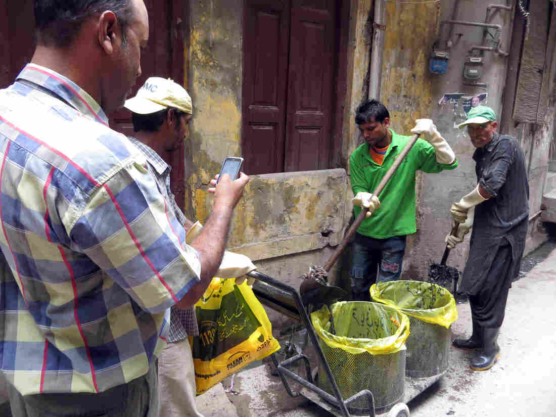 Inspector Mohammad Saleem Taqi takes a photo of sanitation workers as they clear out debris in sewers.
