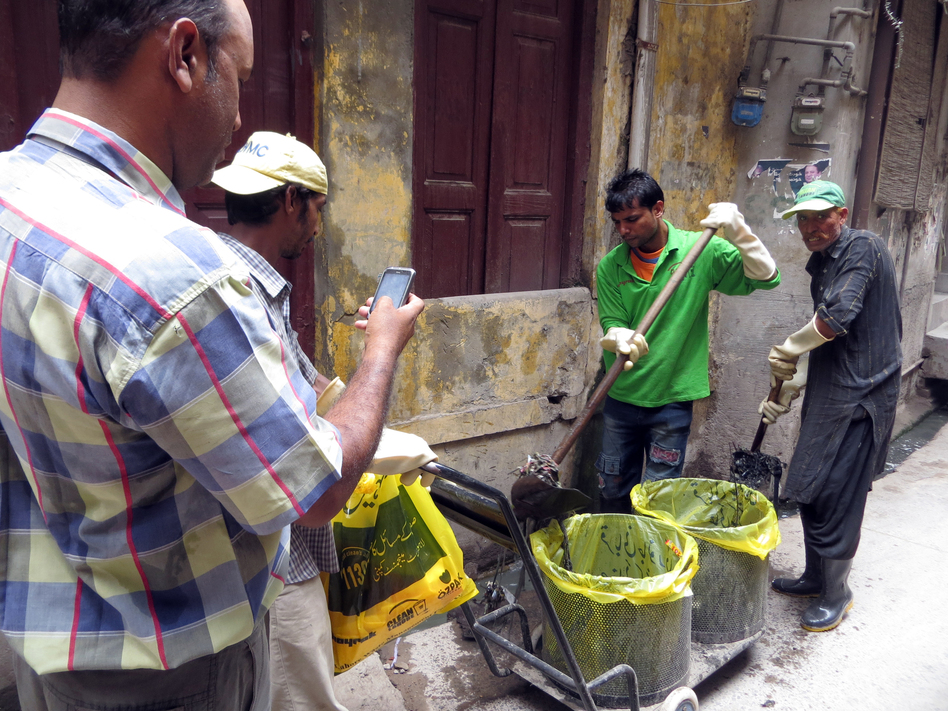 Inspector Mohammad Saleem Taqi takes a photo of sanitation workers as they clear out debris in sewers. The government feeds the photos into a map to track the city's effort to stop dengue fever.