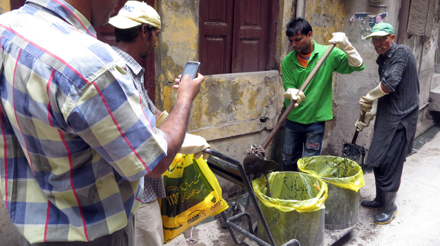 Inspector Mohammad Saleem Taqi takes a photo of sanitation workers as they clear out debris in sewers. The government feeds the photos into a map to track the city's effort to stop dengue fever. (NPR)