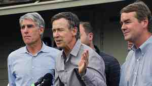 Colorado Gov. John Hickenlooper (center) speaks to members of the media Saturday, alongside Sens. Mark Udall (left) and Michael Bennet, after touring flood-damaged areas by army helicopter.