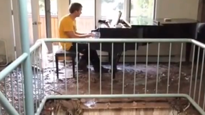 Mark Changaris sits at his piano, after a mudslide wrecked his home.