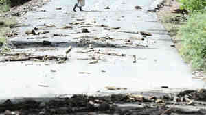 A man walks across the washed-out Wagonwheel Gap Road in Boulder, Colo., on Monday.