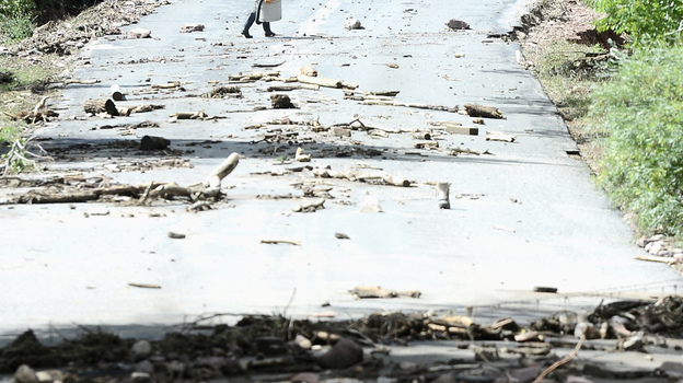 A man walks across the washed-out Wagonwheel Gap Road in Boulder, Colo., on Monday. (Reuters/Landov)