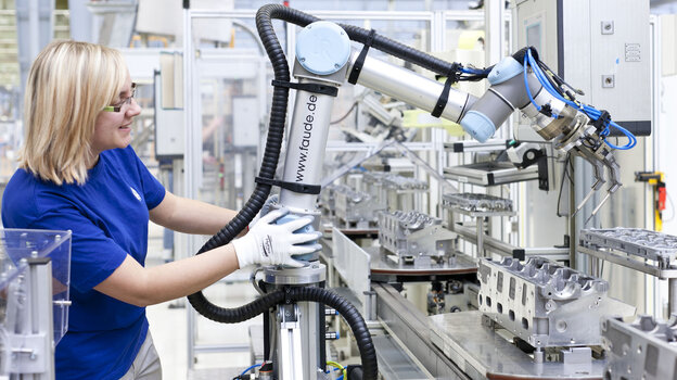 A robot arm helps make engine components at a Volkswagen factory in Germany. For the first time, robots are w