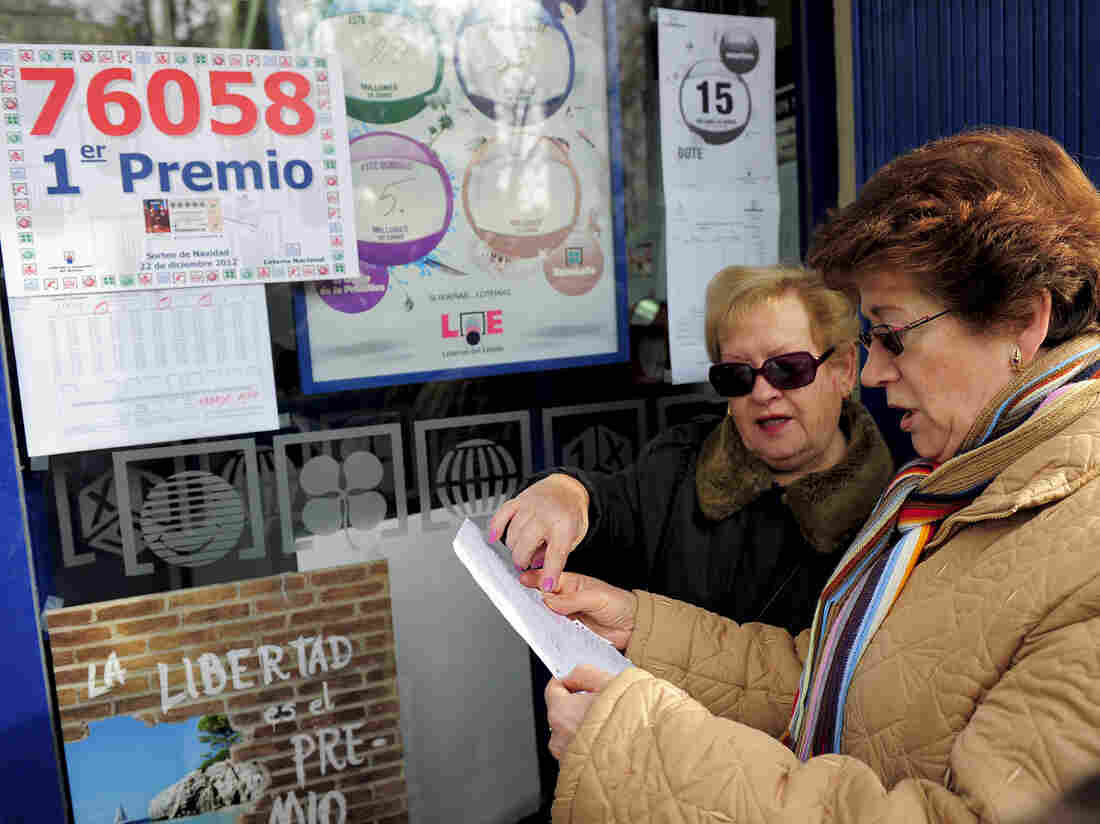 """Women in Barcelona check their numbers for Spain's Christmas lottery, named """"El Gordo"""" (Fat One), in 2012."""