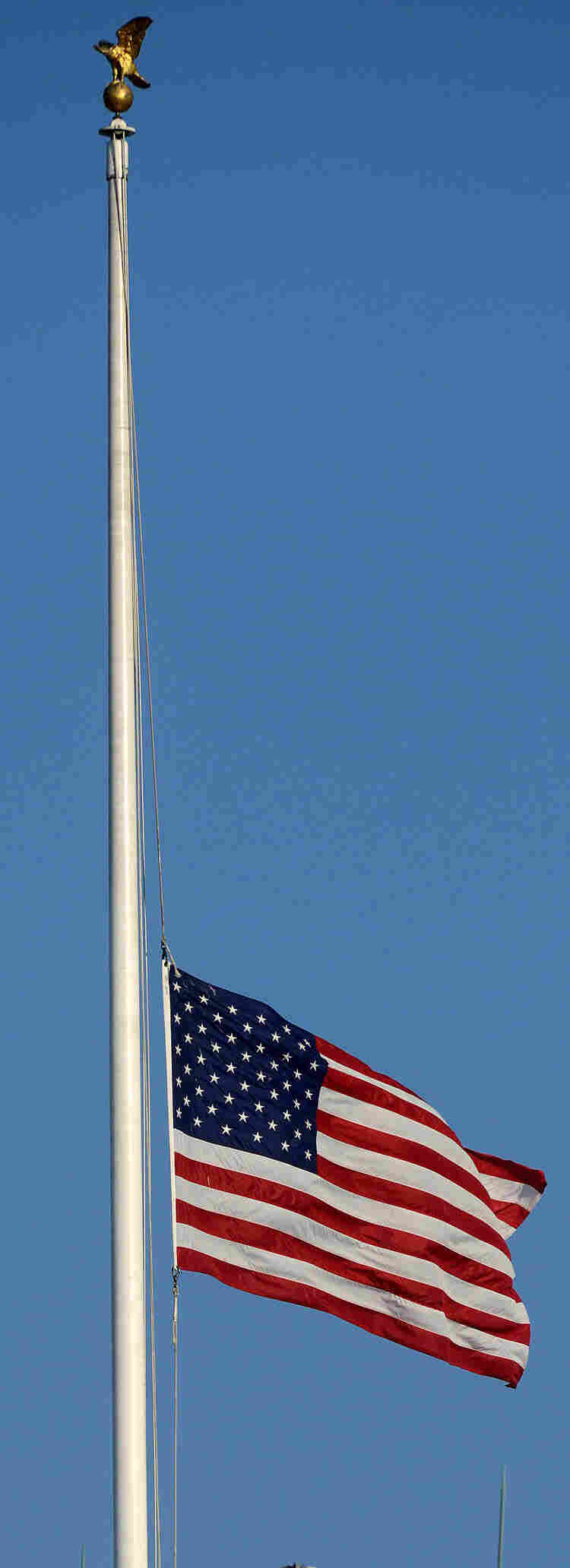 The American flag flies at half-staff atop the White House on Monday.
