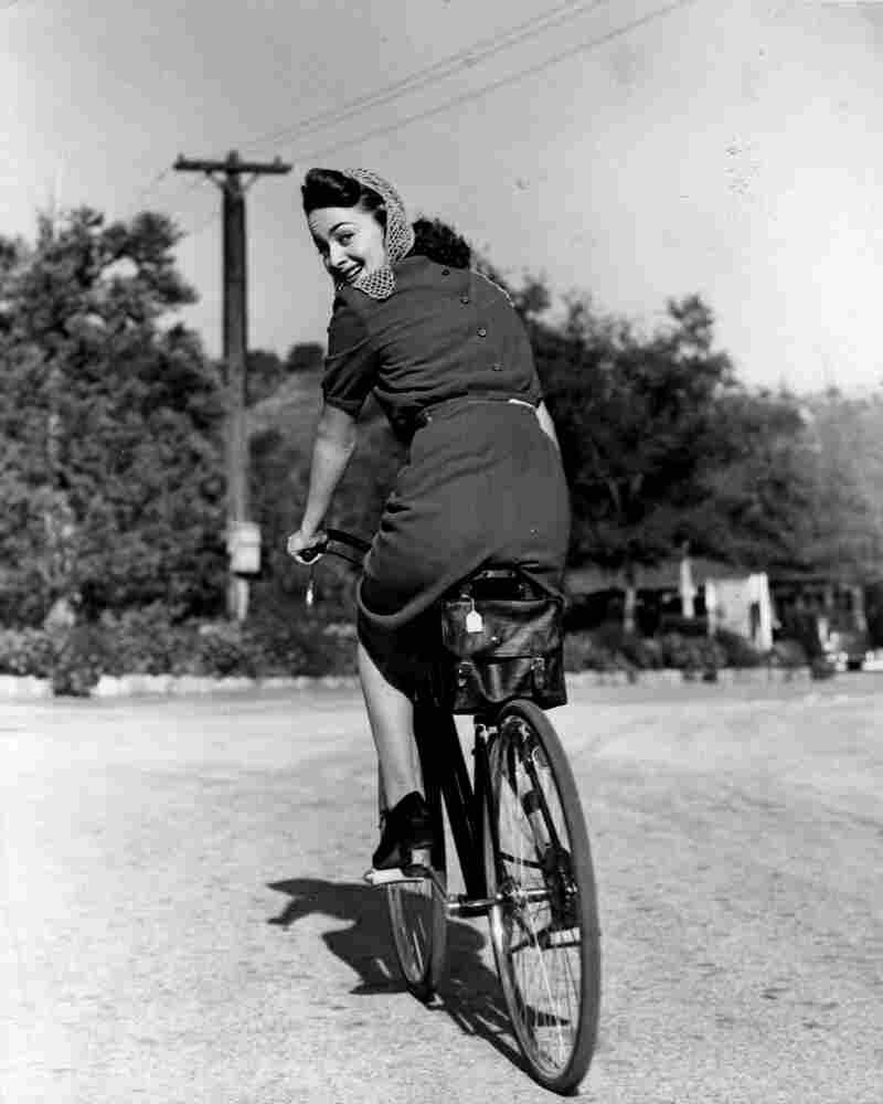 De Havilland rides a bicycle circa 1938.