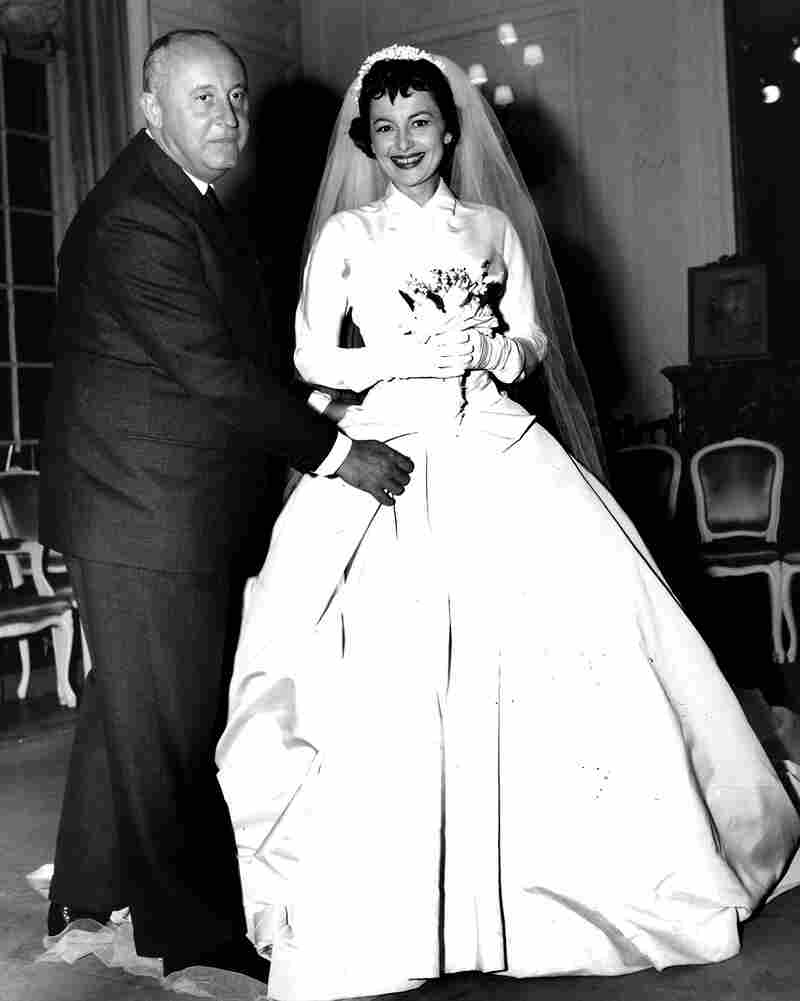 French designer Christian Dior fits de Havilland with a wedding dress for her role in the 1956 film The Ambassador's Daughter.