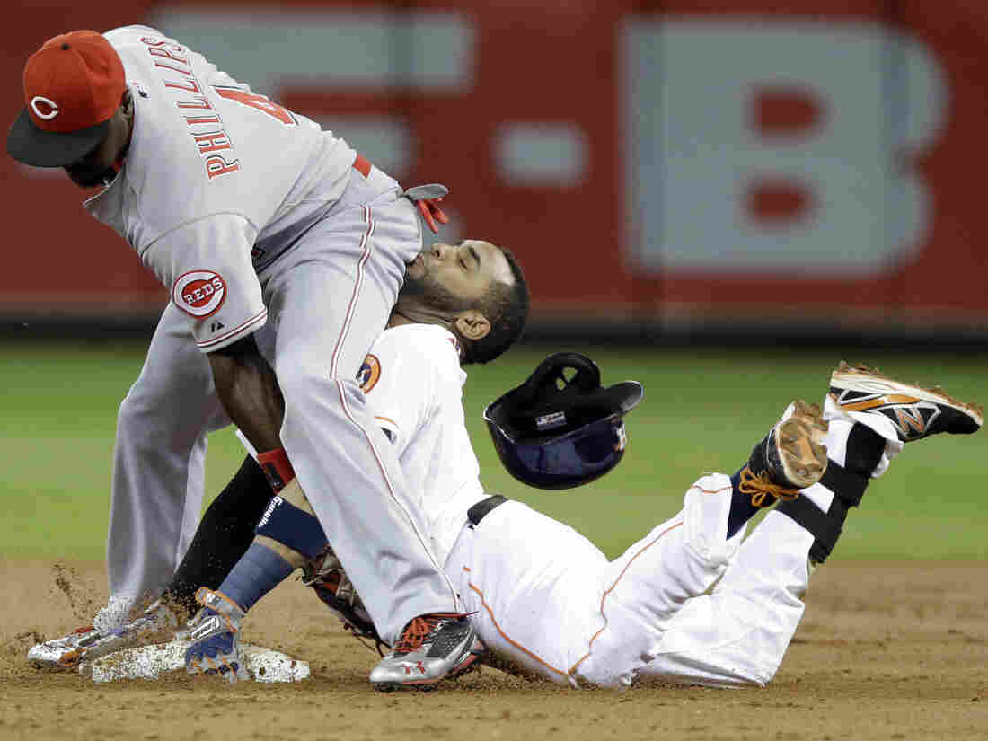 Up close and personal: Cincinnati Reds second baseman Brandon Phillips, left, reaches back to tag out Houston Astros' Jonathan Villar during Tuesday's game in Houston.