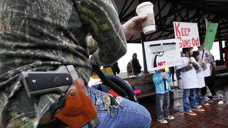 A Starbucks customer — gun on his hip and drink in his hand — watches a rally by gun control advocates, in Seattle in 2010.