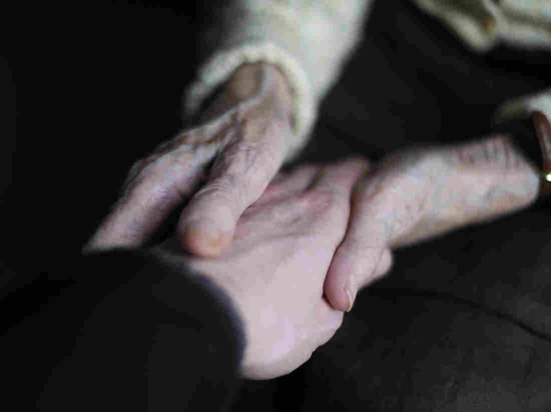 A woman suffering from Alzheimer's disease holds the hand of a relative in a retirement house in Angervilliers, France.