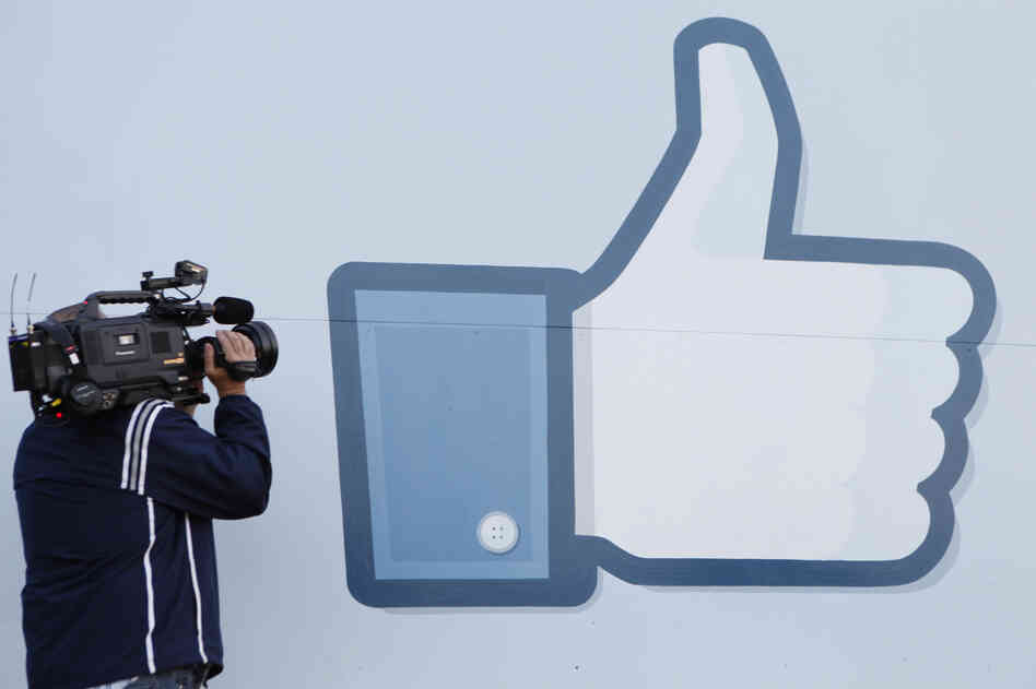 A videographer shoots the side of Facebook's Like Button logo displayed at the entrance of the Facebook headquarters in Menlo Park, Calif.