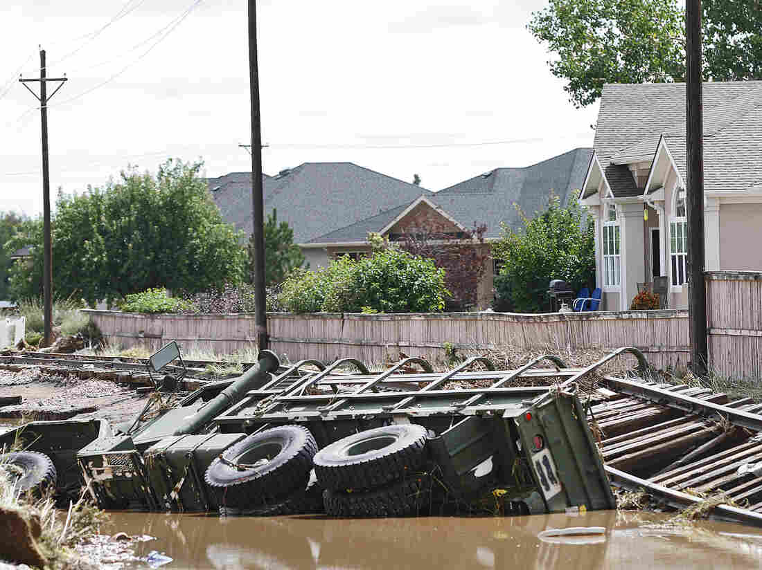 A military vehicle was on its side in a ditch in Longmont, Colo., on Tuesday after being washed away by floodwaters.