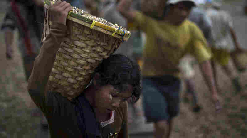 A child carries a basket of stones while unloading a quarry boat with adult workers at a port in Yangon, Myanm