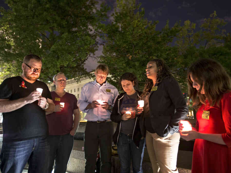 A small group holds a candlelight vigil Monday on Washington's Freedom Plaza to remember the victims of the D.C. Navy Yard shooting.