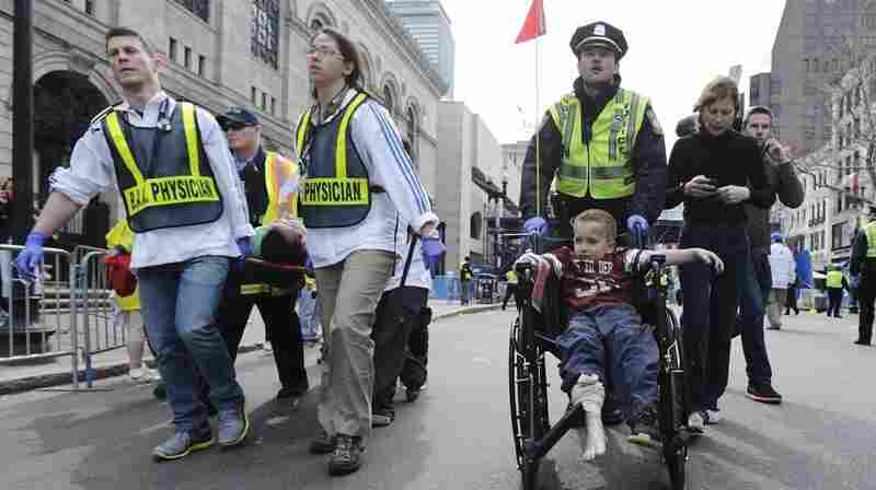 A Boston police officer wheels an injured boy down Boylston Street as medical workers carry an injured runner after the Boston Marathon bombing in April.