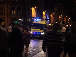 An ambulance makes its way through revelers in Cardiff city cent