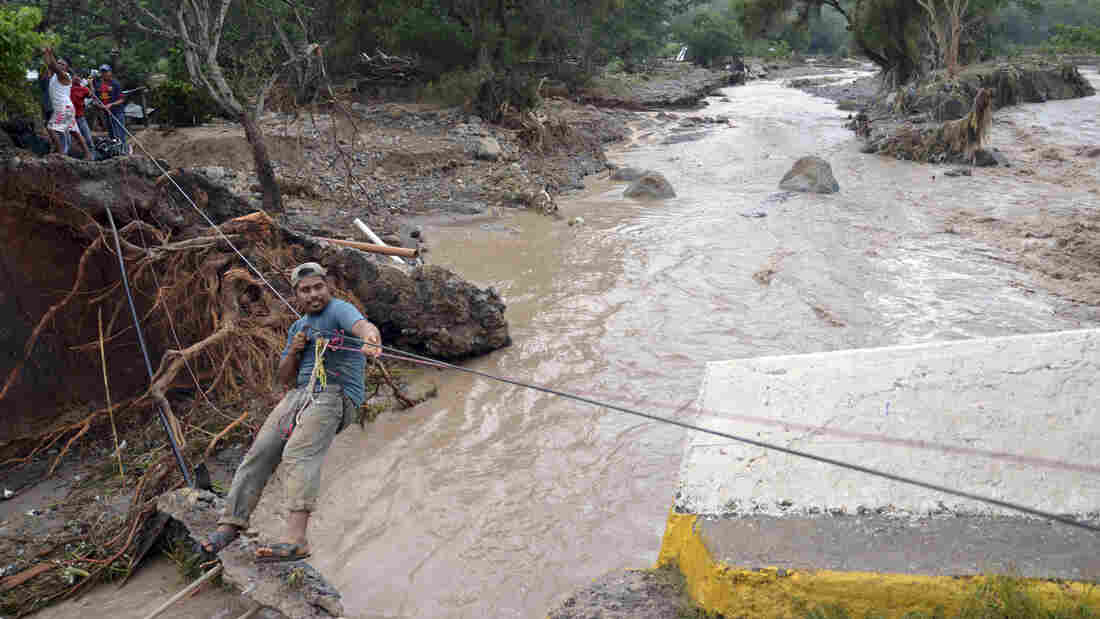 Near the town of Petaquillas, Mexico, a man held on to a line Wednesday as he crossed a stream swollen by rain dumped by the storm Manuel.