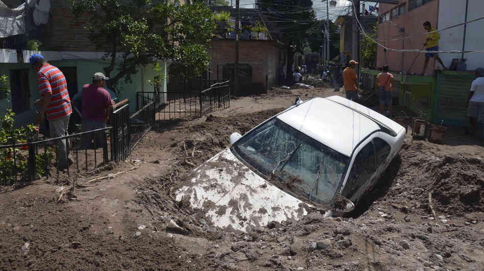 A car lays buried in mud after flooding triggered by Hurricane Manuel in Chilpancingo, Mexico.
