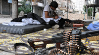 A rebel fighter cleans his weapon in the northern Syrian city of Aleppo Friday. Syria's civil war continues, even as the country follows a schedule of releasing information on its chemical weapons program.